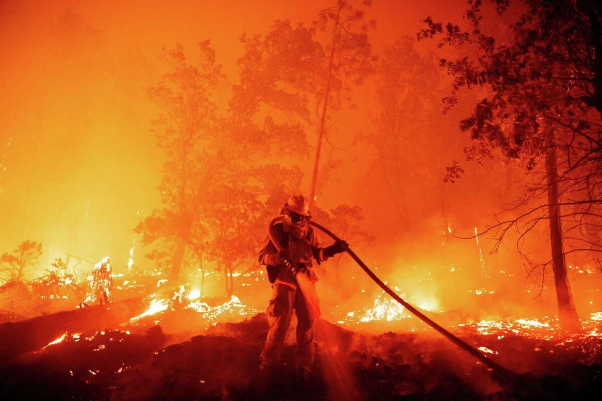 A firefighter douses flames as they push towards homes during the Creek fire in the Cascadel Woods area of unincorporated Madera County, California on September 7, 2020. (JOSH EDELSON / AFP)