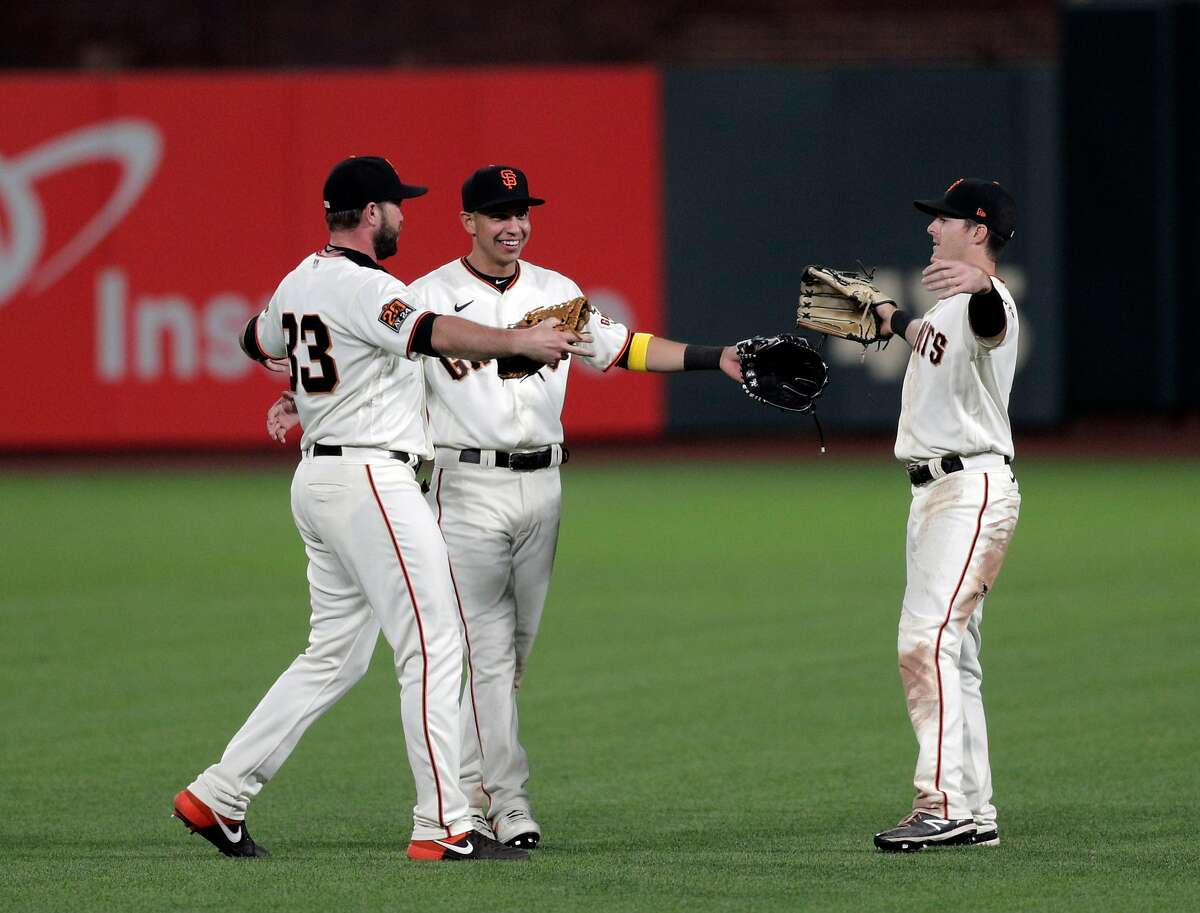 Giants outfielders Darin Ruf (33) Mauricio Dubon (1) and Mike Yastzemski (5) give each other air hugs after the San Francisco Giants defeated the Arizona Diamondbacks 4-2 at Oracle Park in San Francisco Calif., on Monday, September 7, 2020.