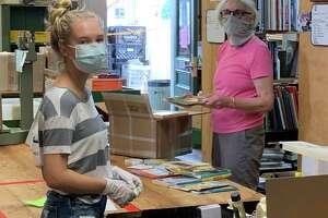 Darien Book Aid volunteers Mia Gallo of Darien, left, and Kitty Graves of Westport.