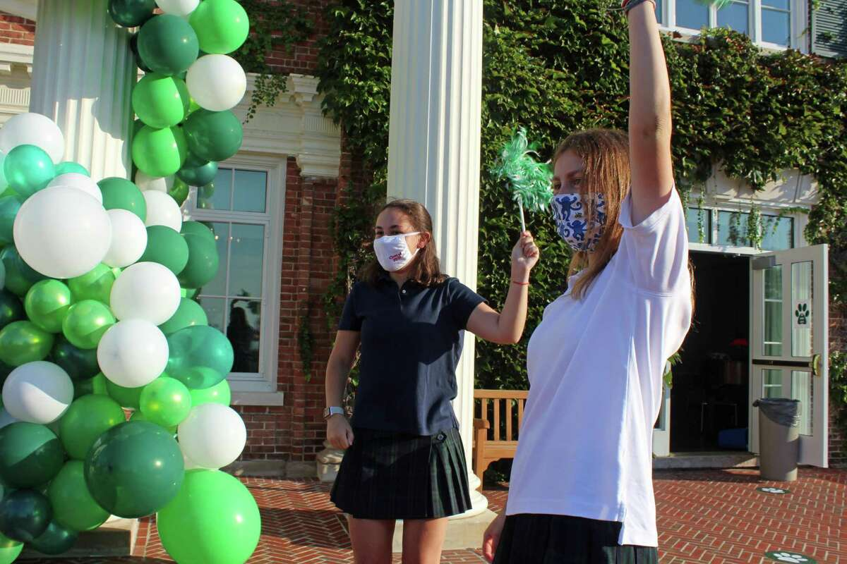 Sacred Heart Greenwich seniors Hadley Noonan and Ursula Vollmer, both 17, greet classmates on the first day of school, Sept. 8, 2020, in Greenwich, Conn. In front of Nancy Salisbury Hall, a short distance from where Frazier stood, was Karen Panarella, dean of Sacred Heart's Upper School. With the pandemic, there was undoubtedly an added element of stress this year, Panarella said. But it was also more exciting.