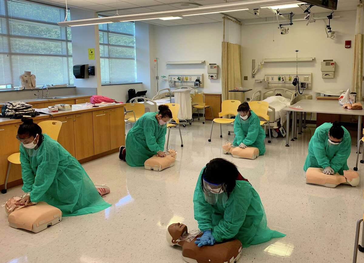 Certified nurse aide students donning PPE learn CPR at Norwalk Community College.