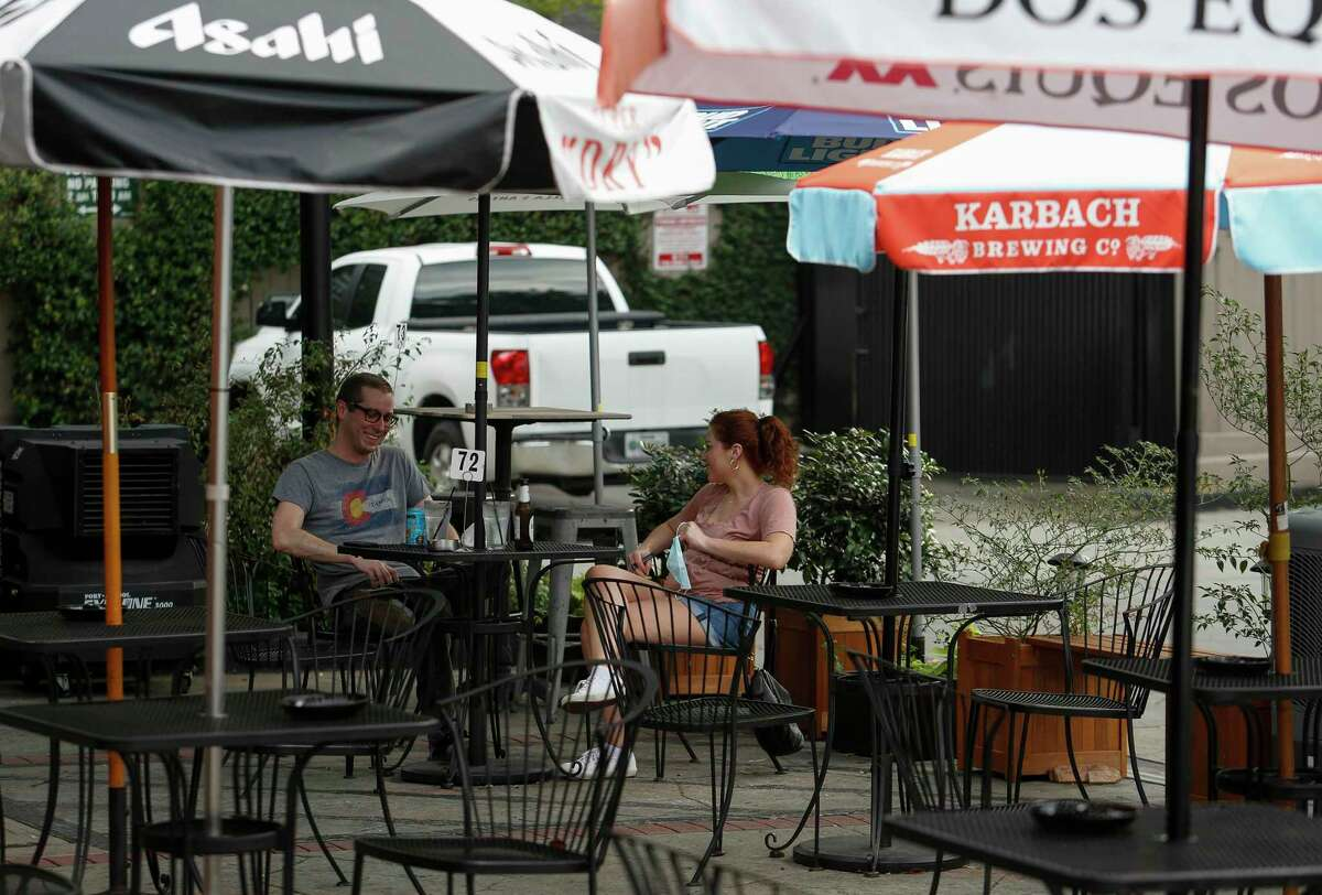 Derek Rowan, left, and Allison Ballentine, center, chat while waiting for their order at The Phoenix on Westheimer. The brew pub has used five parking spaces to add nine extra patio dining tables. The expanded patio dining options has been a lifeline to the restaurant as more people opt to sit outside.