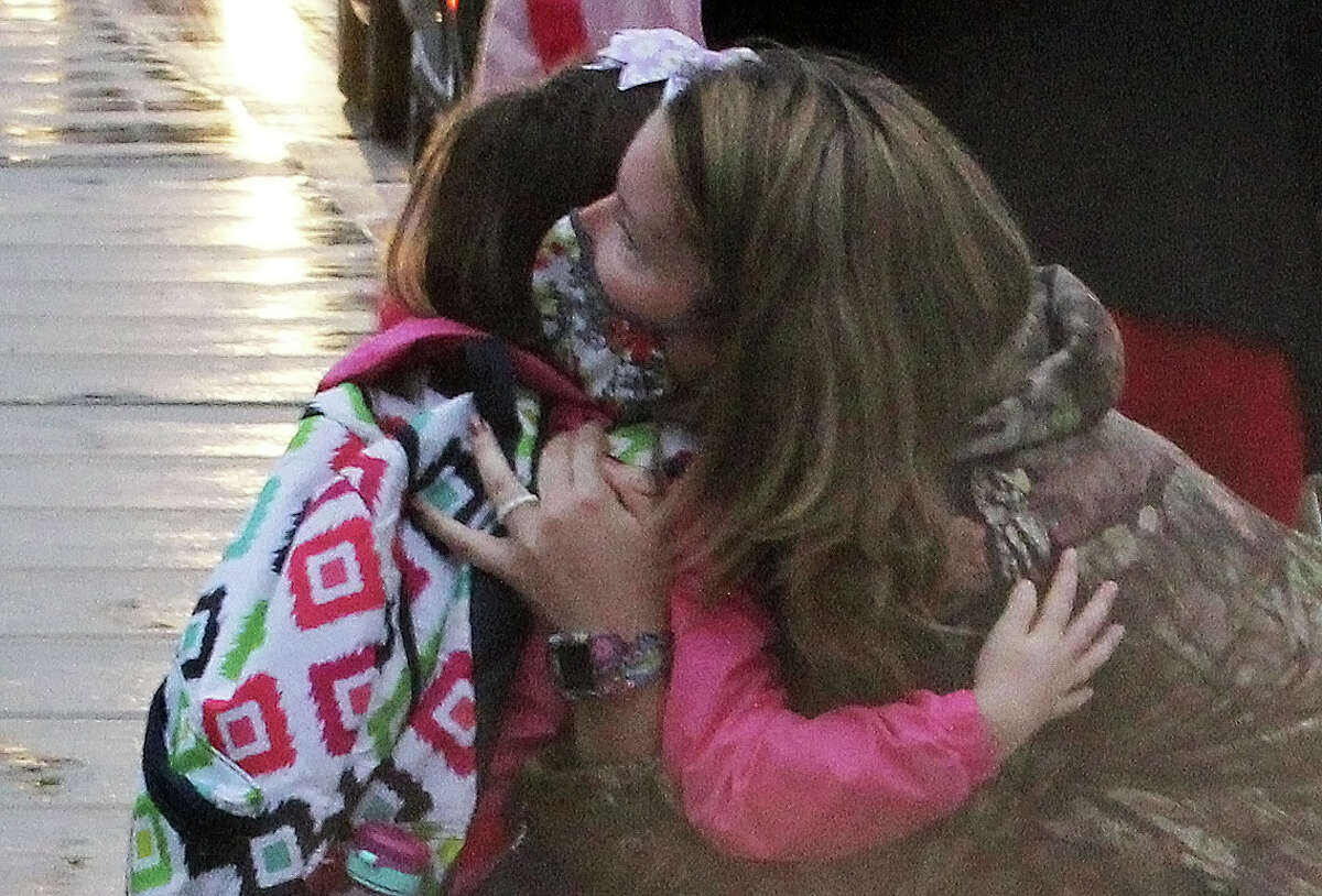 Umbrellas and hugs were the order of the day Tuesday morning in Pigeon as Laker Schools students arrived for the first day of classes.