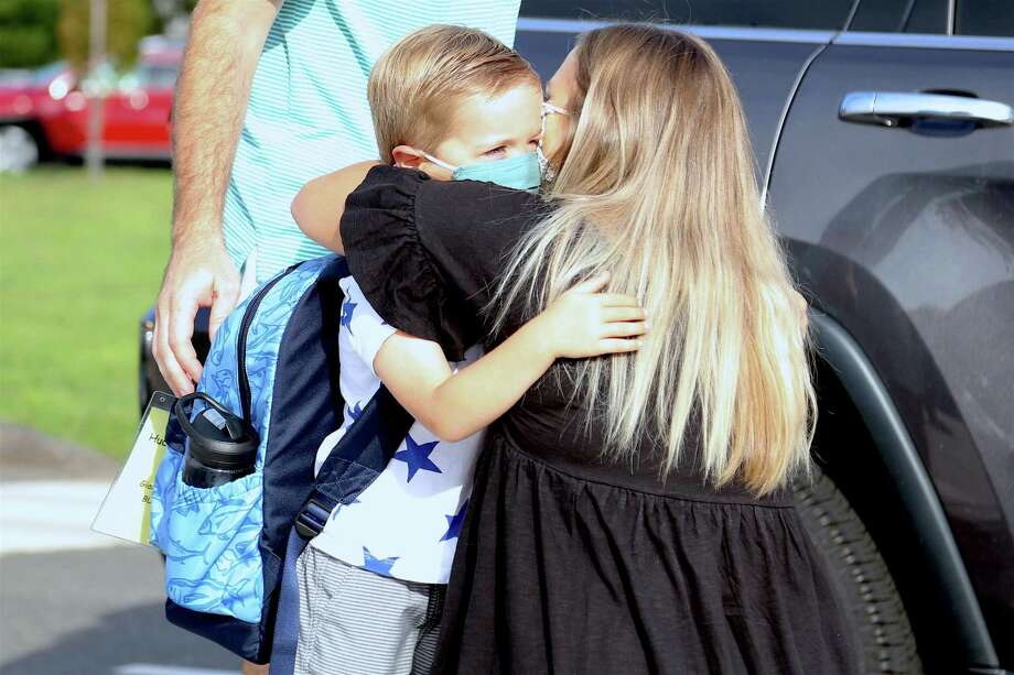 A tearful Kellin Frost hugs her son Hudson, 4, who is beginning his first day of kindergarten at Miller-Driscoll on Sept. 8, 2020, in Wilton, Conn.