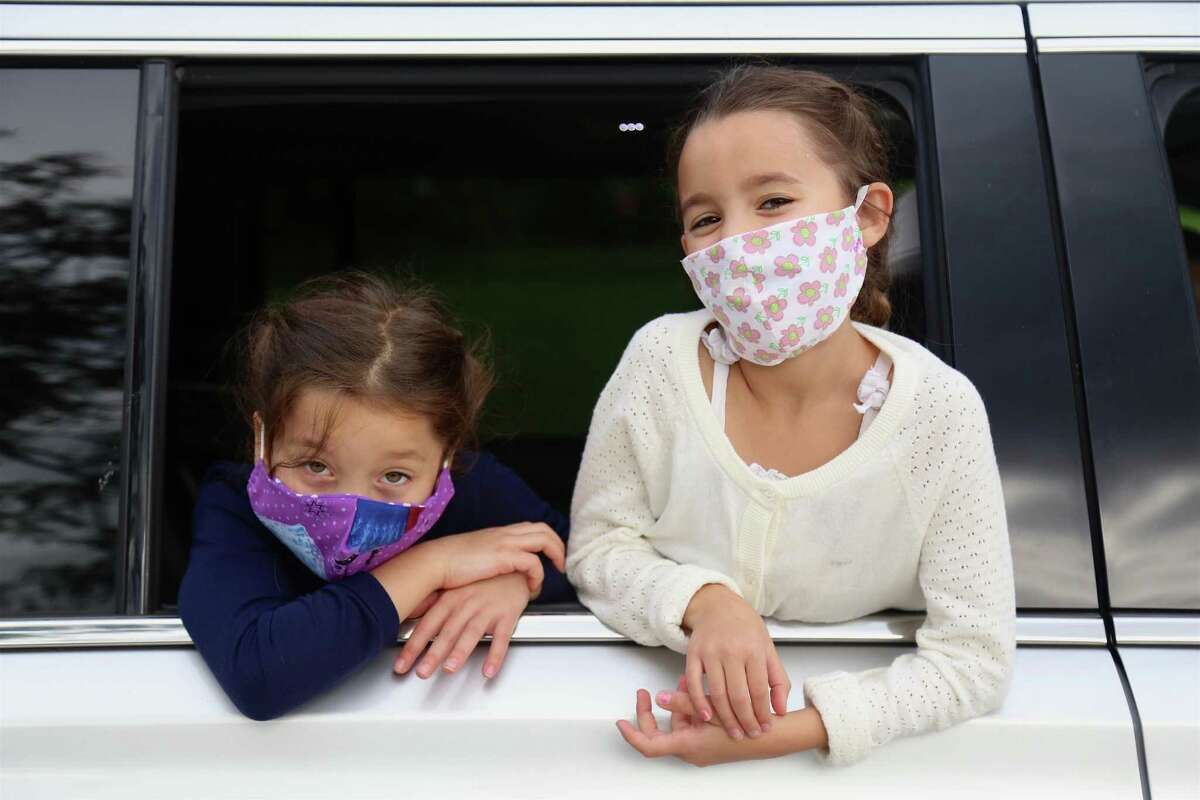 Twins Aurora, left, and Winnie Gulati, 6, wear masks on the first day of school at Miller-Driscoll on Sept. 8.