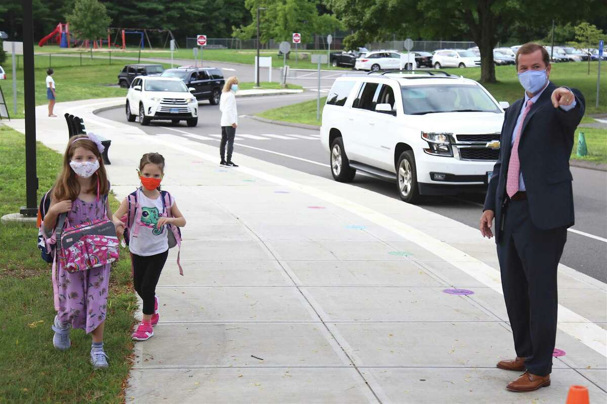 Superintendent of School Kevin Smith directs two students into school for their first day of in-person class at Miller-Driscoll on Sept. 8, 2020, in Wilton, Conn.
