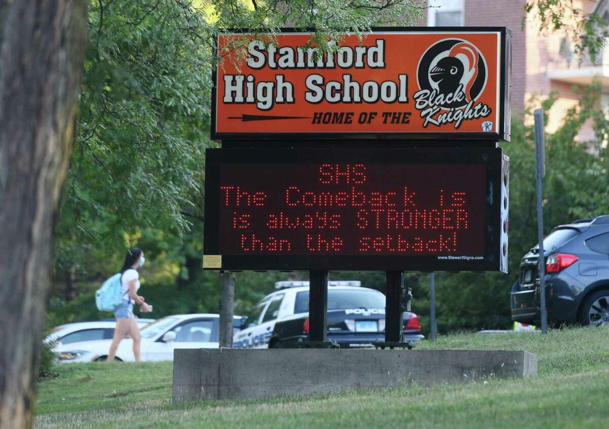 A positive message is displayed as students enter school on the first day of the 2020-2021 school year at Stamford High School in Stamford, Conn. Tuesday, Sept. 8, 2020. As a coronavirus precaution, students will be split into two groups to attend classes every other day. On days when they are not physically in class, students will learn remotely.