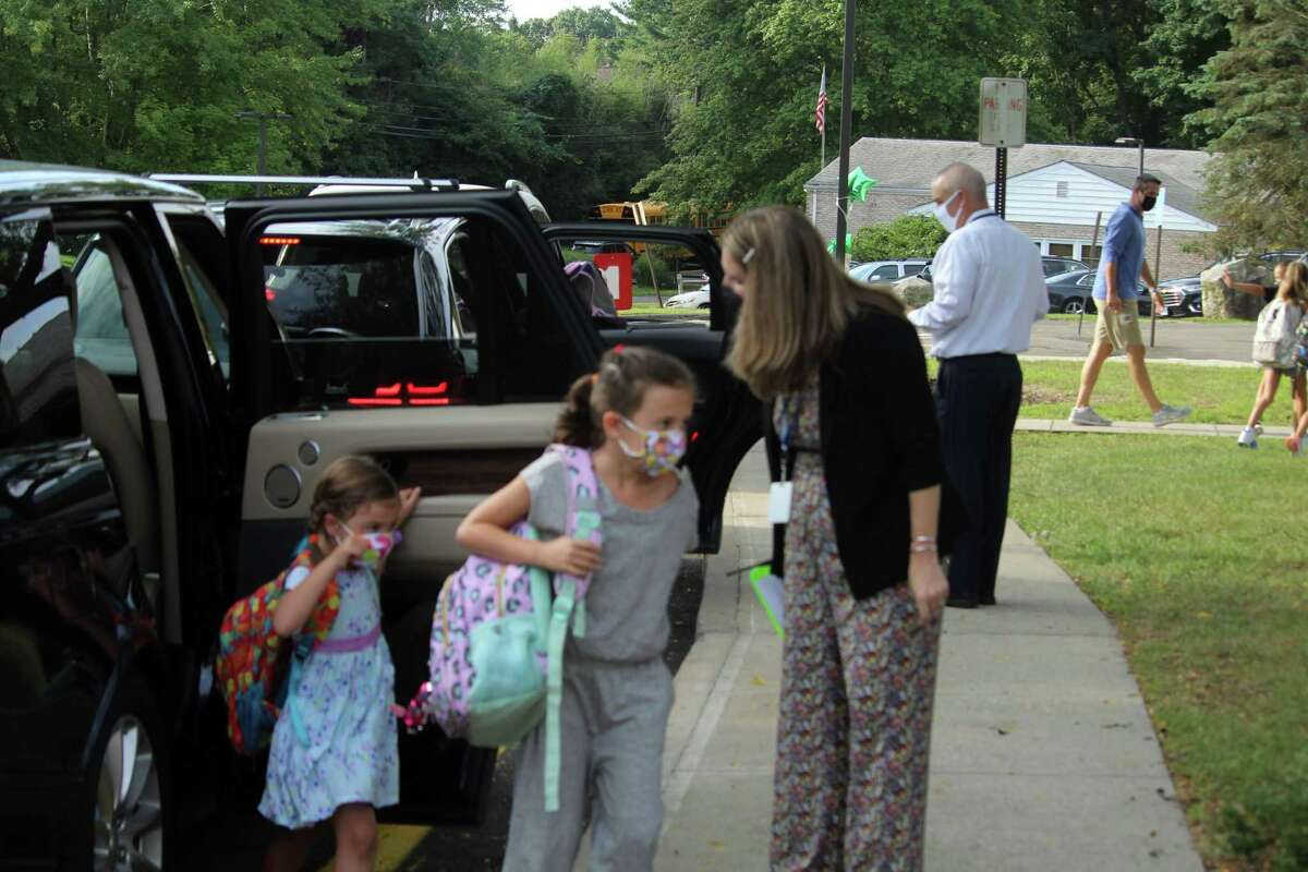 """Coleytown Elementary School principal Janna Sirowich helped welcome students on their first day back at school. Taken Sept. 8, 2020 in Westport, Conn. Students stepped off buses and out of cars with their back packs and a colorful assortment of masks for their first day back. Several teachers and administrators shared their joy with families as they welcomed everybody outside the school. """"We are so excited for this,"""" Janna Sirowich, principal of Coleytown Elementary School, said. """"No one becomes an educator to work at home without seeing children. We are so thrilled to welcome everyone back."""" Sirowich said staff has spent the past two weeks discussing student engagement, health and safety protocols and building relationships."""