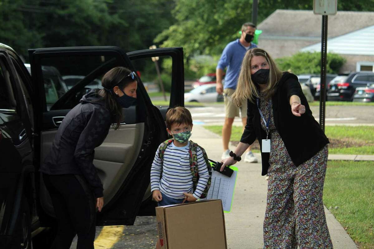"""Coleytown Elementary School principal Janna Sirowich assists a family on their first day back at school. Taken Sept. 8, 2020 in Westport, Conn. Sirowich said new students are paired with buddies in school for support and to help with any questions. The school will also host a variety of new family activities throughout the next month, she said. """"We're really excited to have all the new families here and all the new students here,"""" Sirowich said. """"Coleytown is growing and we're happy about that."""" Sirowich said parents and staff members set the temperature for the children. """"If we are modeling positivity and modeling that we are excited to come back, they feel that,"""" she said."""