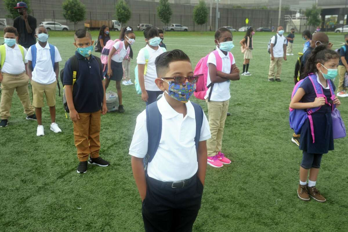 Third grader Angelo Barrera and his classmates line up a safe social distance prior to entering Roosevelt School for the first days of class, in Bridgeport, Conn. Sept. 8, 2020.