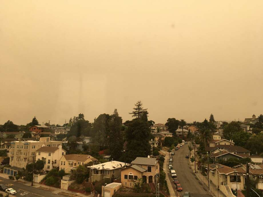 A view from a window in Oakland Tuesday morning showed a sky with an eerie yellow glow. Photo: Douglas Zimmerman / SFGATE
