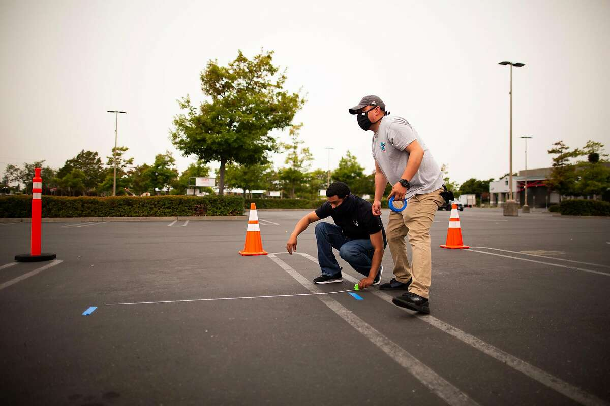 Guillermo Sabas (left) and Jeovanny Torrez measure and lay down tape to mark 6 feet for social distancing at a PG&E community resource center in the parking lot of Costco, Santa Rosa, California, September 8th, 2020. The center is providing water, snacks, charging stations, shade and other items to people who lost power to PG&E power cuts to prevent wildfires.