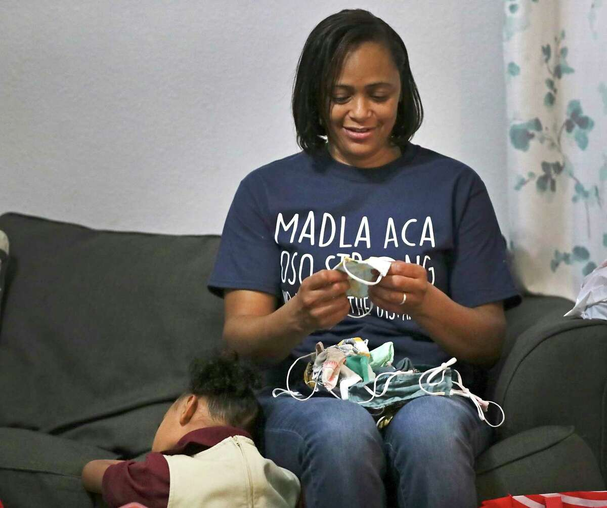 Danyal Nolasco, a teacher at Frank L. Madla Accelerated Collegiate Academy, sorts out masks at home to give to her three children before leaving for their first in-person day of school. Her daughter Alyssa, 5, takes a quick nap next to her before they leave.