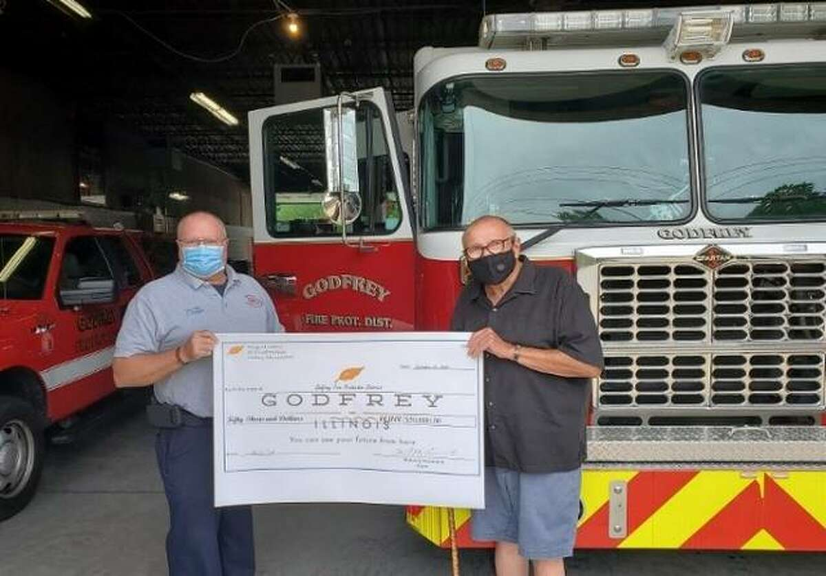 Godfrey Mayor Mike McCormick presents Chief Eric Cranmer with a check for the new KME Rescue Pumper.