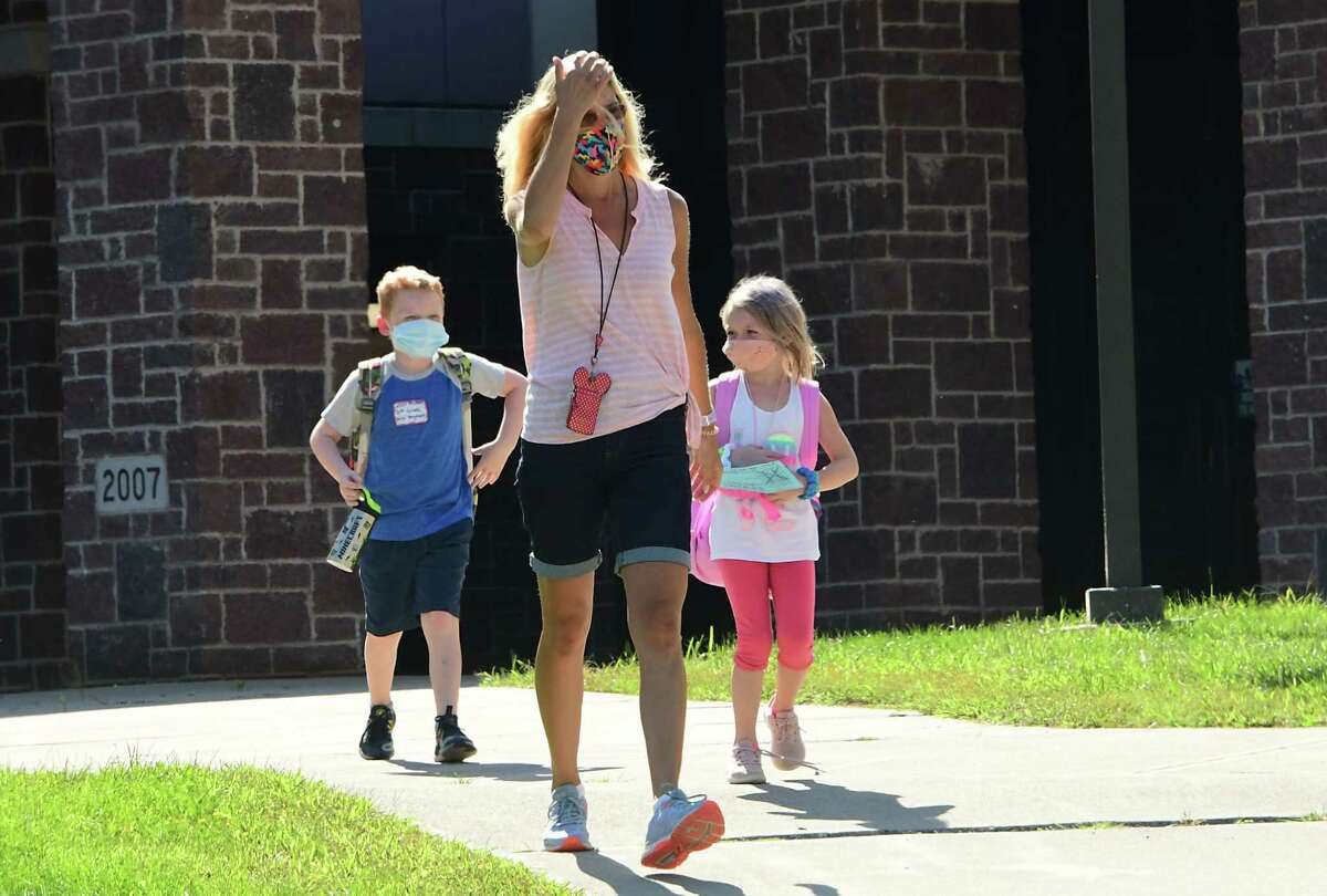 A teacher brings a couple students out to their parents who are picking them up from Rensselaer School District on the first day of classes on Tuesday, Sept. 8, 2020 in Rensselaer, N.Y. (Lori Van Buren/Times Union)