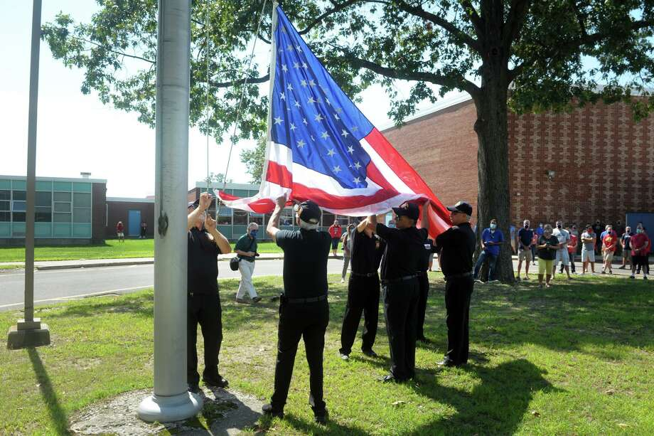 Members of VFW Post 9460 raise a new American flag in front of Bunnell High School, in Stratford, Conn. Sept. 8, 2020. Photo: Ned Gerard / Hearst Connecticut Media / Connecticut Post
