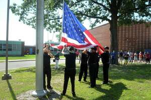 Members of VFW Post 9460 raise a new American flag in front of Bunnell High School, in Stratford, Conn. Sept. 8, 2020.