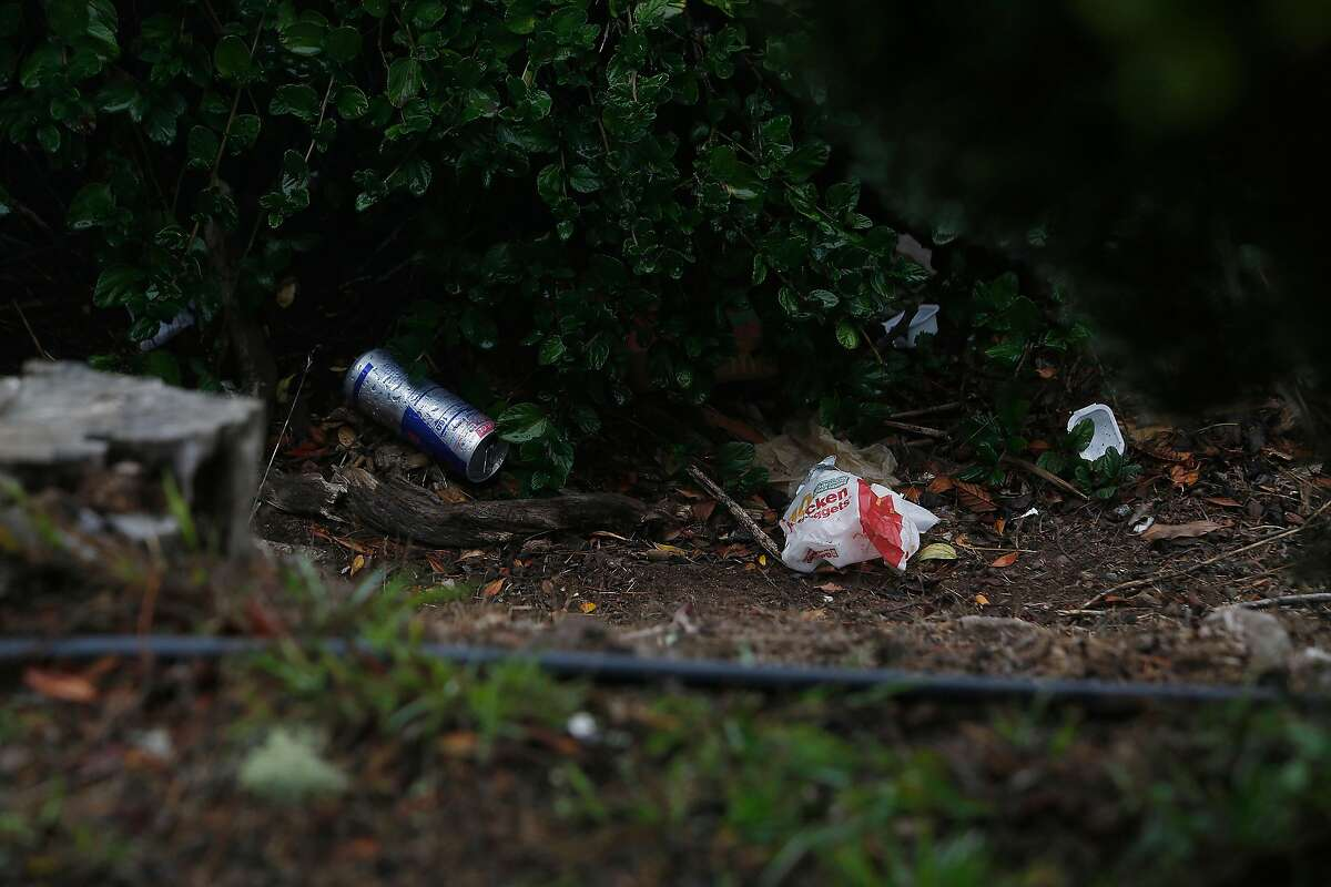 A can and food wrappings are seen along Burnett Avenue near the road closure at Twin Peaks Boulevard and Burnett Avenue on Monday, August 31, 2020 in San Francisco, Calif.