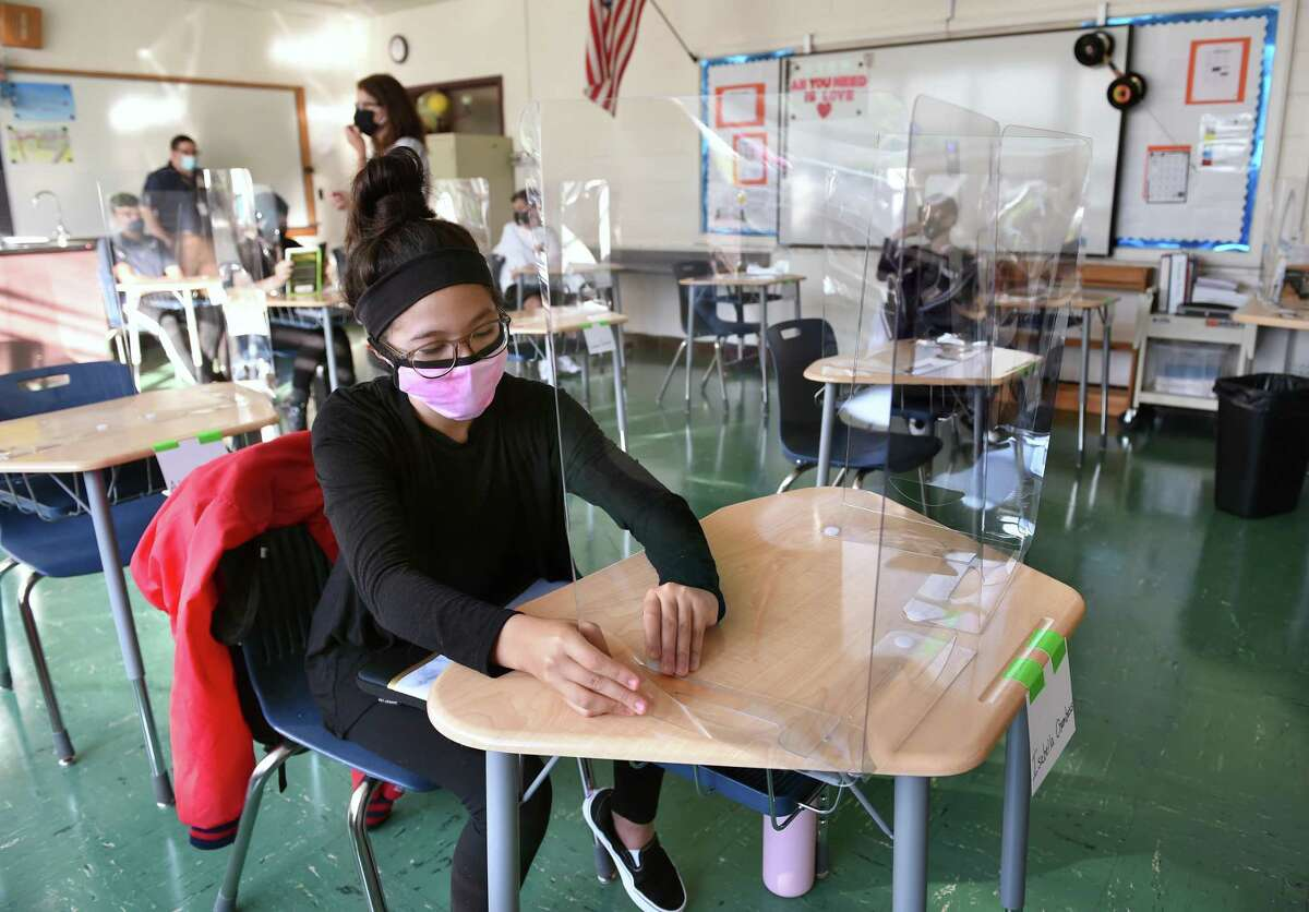 Isabella Chambasis, 13, adjusts the plastic shield on her desk in eighth grade science class on the first day of school Joseph Melillo Middle School in East Haven on September 8, 2020. Total school enrollment in Connecticut 2014-15: 546,349 | 2015-16: 541,815 | 2016-17: 538,899 |2017-18: 535,025 | 2018-19: 1530,612 | 2019-20: 527,829 | 2020-21  (preliminary estimate): 512,39 RELATED: Officials: More parents opt to keep pre-K, kindergartners out of school during COVID pandemic Source: Connecticut Board of Education