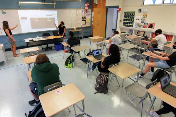 Teacher Lauren Marchello, left, teaches Modern Global Studies during the first day of school at Fairfield Ludlowe High School in Fairfield, Conn., on Tuesday Sept. 8, 2020. Also working with Marchello is secondary teacher Aaryn Signorile.