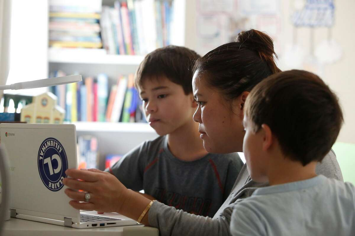 Cathy Tran, (center) helps son Charlie Klos (left), 8, try to figure out why he is unable to unmute himself during a school zoom session after son James