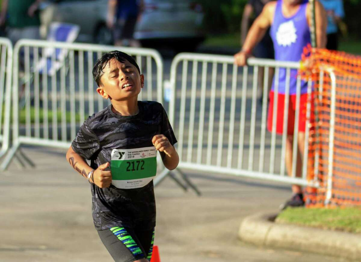 """The in-person YMCA Kids Triathlon, a popular short-course event for children ages 5 years old to 15 who are just learning the sport, has been canceled and will instead be conducted in a """"virtual"""" manner, with kids doing the events alone with a parent or coach timing their effort. Registration ends Oct. 21. A triathlete competes in the running portion of the YMCA Kids Triathlon on Saturday, July 20, 2019 at The Woodlands Family YMCA at Branch Crossing in The Woodlands."""