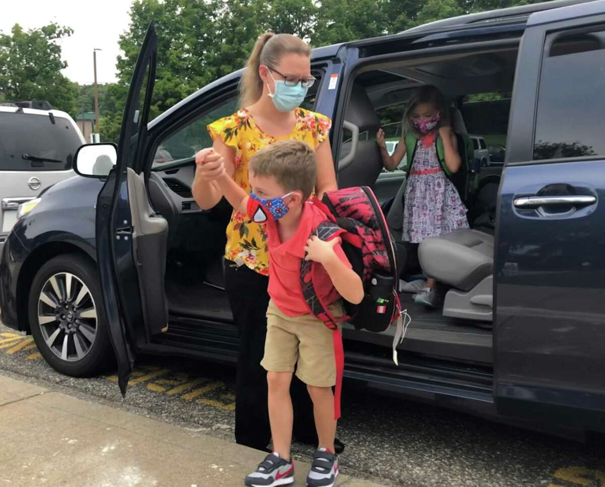 Courtney Kennedy was among the parents at the student drop-off area at Northville Elementary School. Above, she helps her children, twins Owen and Teagan, prepare for their first day as first graders.
