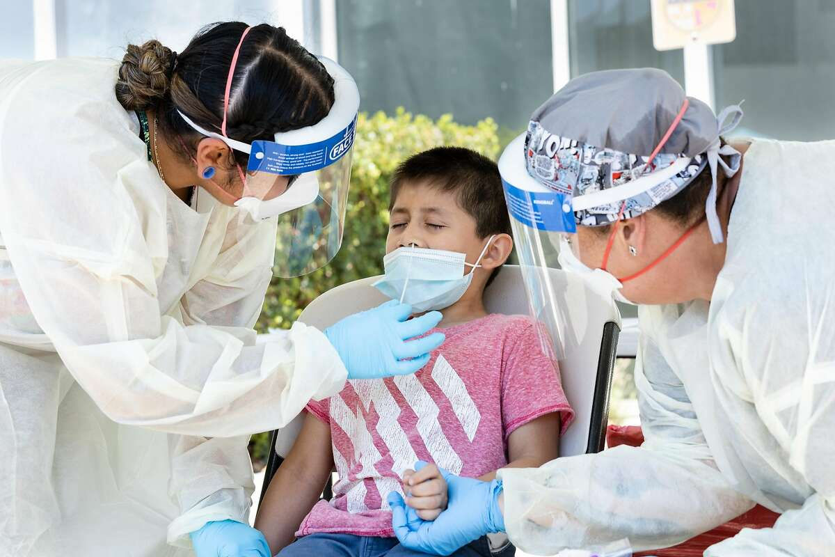 Nurse Adriana Torres (left) gives patient Brando Gonzalez a COVID-19 test while Nurse Michelle Green comforts him at the Marin Community Clinics testing site on Wednesday, August 19, 2020, in San Rafael, Calif.