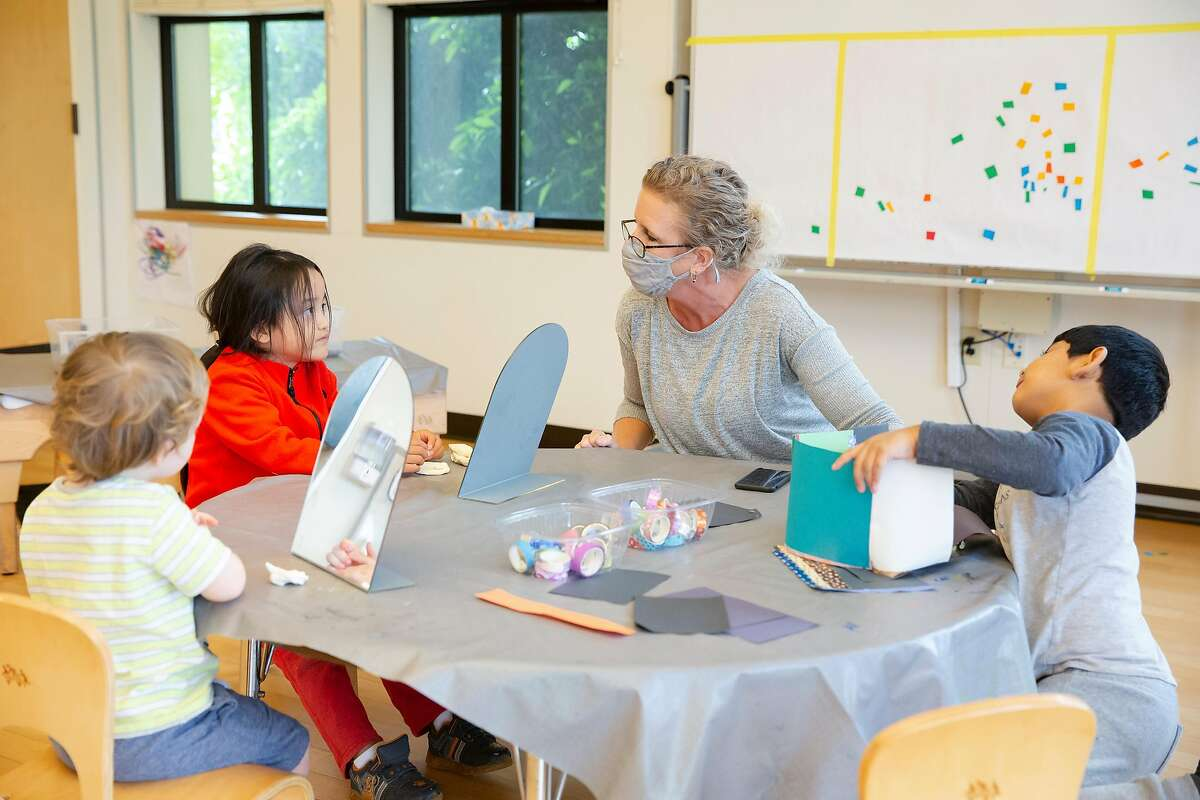 Susan Meyer, a teacher at Holy Family Day Home, works with two kindergarten students, Christopher Ramirez-Ojeda and Andy Beltor during preschool hours at Holy Family Day Home in San Francisco, Calif. on September 3, 2020.