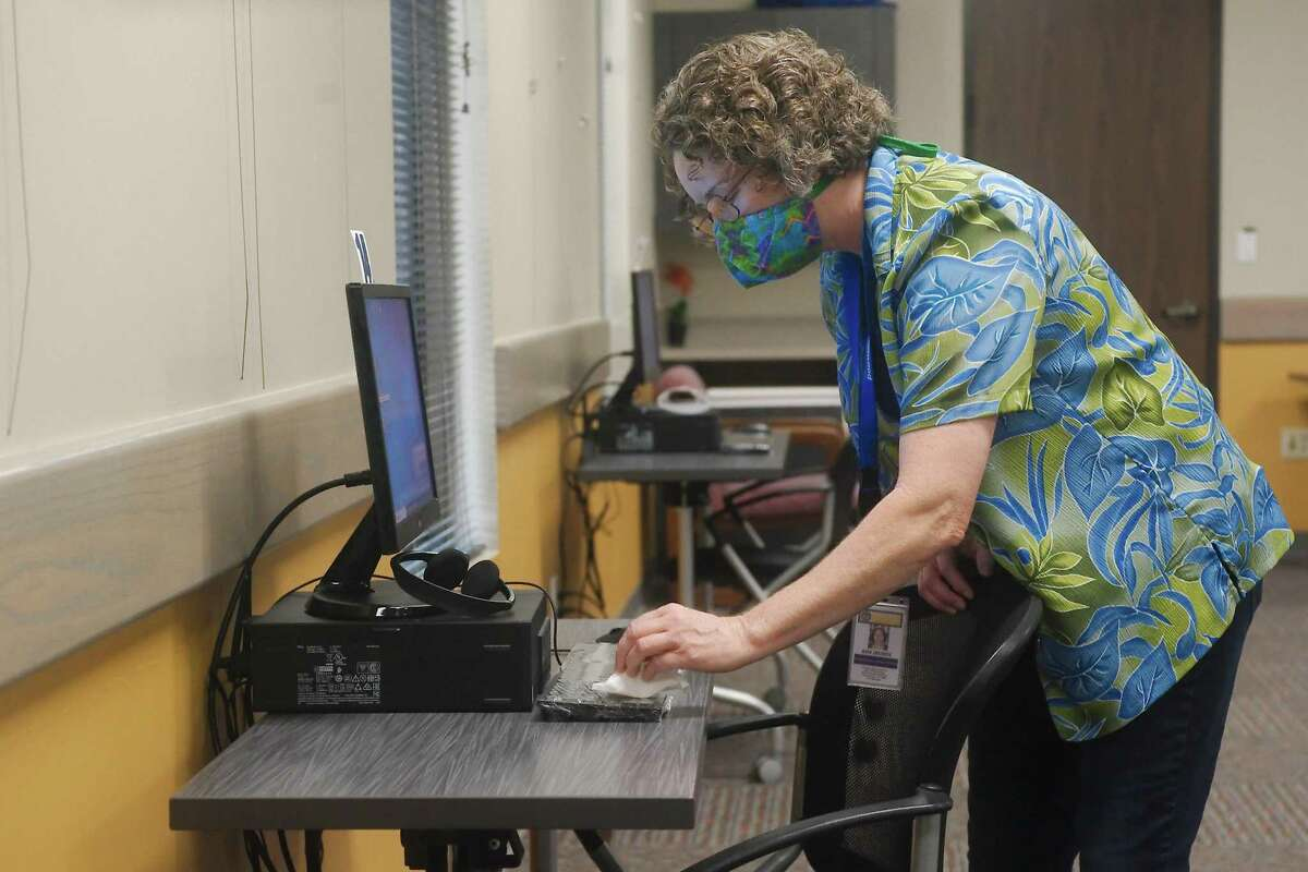 Friendswood Reference Librarian Kim Zrubek disinfects a keyboard as she prepares a computer work station for use in the computer room at the Friendswood Library, which recently reopened.
