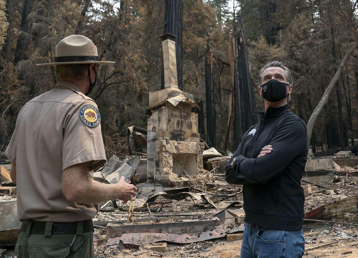 California Gov. Gavin Newsom, right, listens as Santa Cruz State Park Superintendent Chris Spohrer, left, talks about the fire damage to Big Basin Redwoods State Park, Tuesday, Sept. 1, 2020, in Boulder Creek, Calif. (LiPo Ching/San Francisco Chronicle via AP)