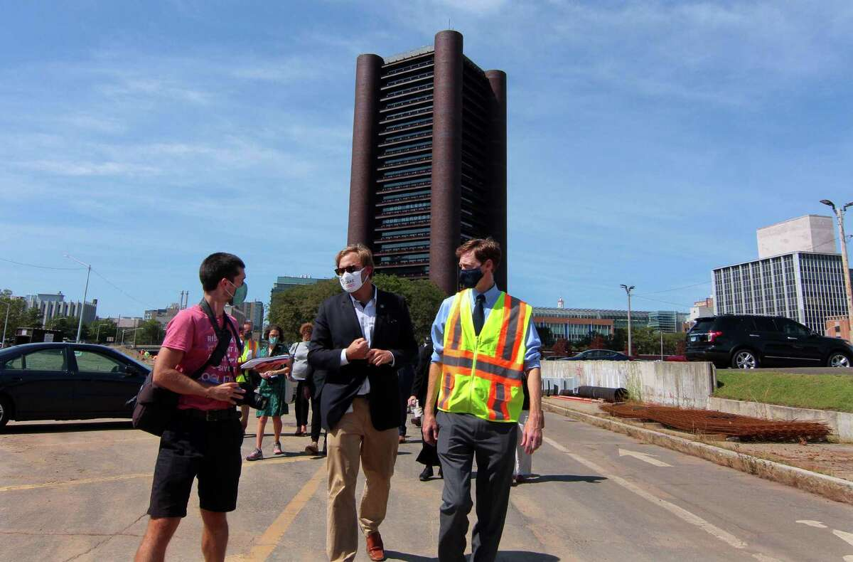 Doug Hausladen, city director of Transportation, Traffic & Parking, center, and New Haven Mayor Justin Elicker take part in a walking tour to see progress on Phase 2 of the Downtown Crossing redevelopment project in New Haven, Conn., Sept. 8, 2020.
