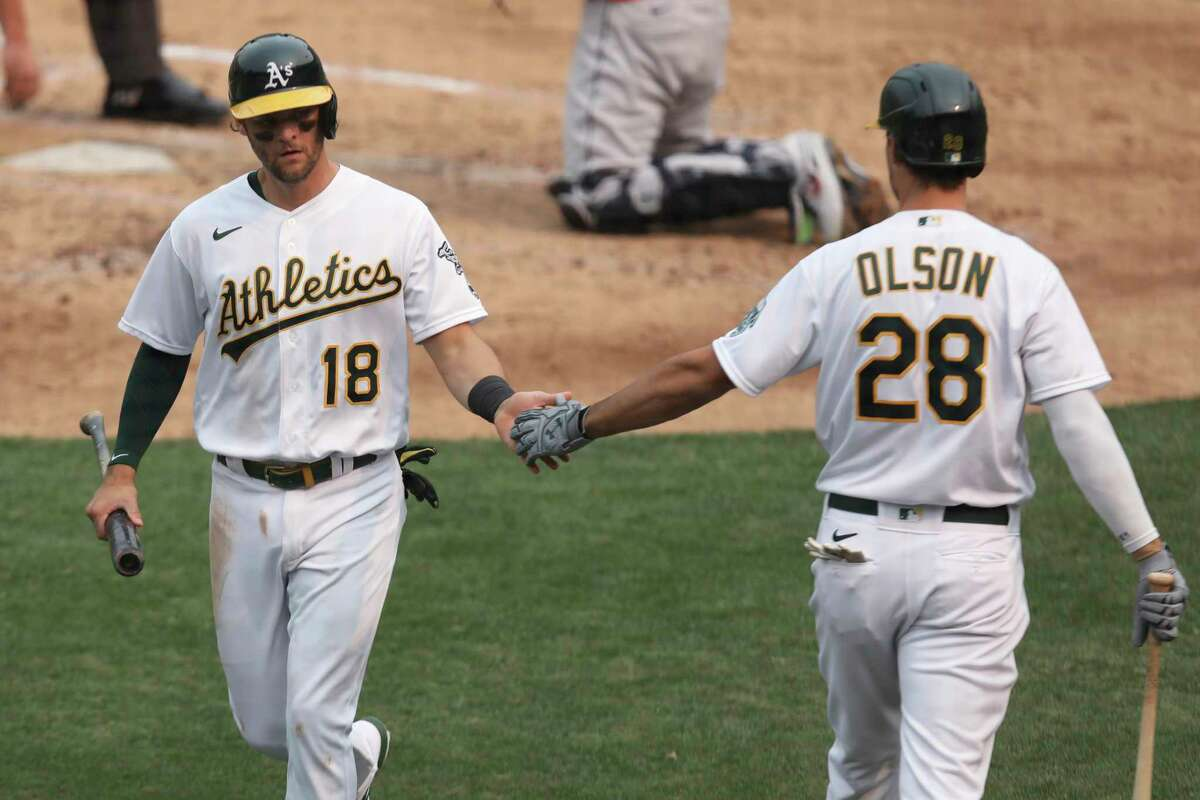 Oakland Athletics' Chad Pinder, left, celebrates with Matt Olson after scoring on a single by Ramon Laureano against the Houston Astros during the third inning of the first baseball game of a doubleheader in Oakland, Calif., Tuesday, Sept. 8, 2020. (AP Photo/Jed Jacobsohn)