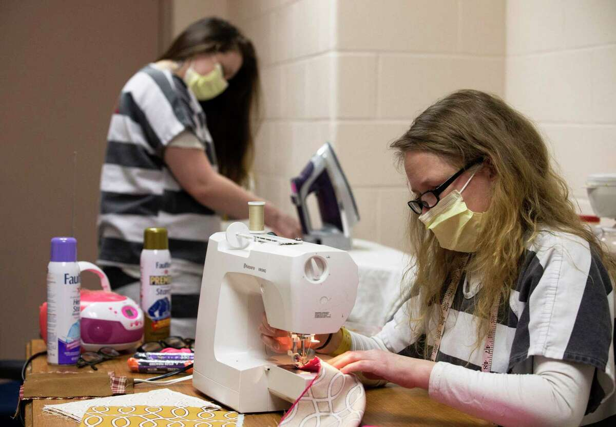 Fort Bend County Jail inmates Samantha Runke, left, and Andrea Pesce make cloth masks Thursday, April 9, 2020, in Richmond, Texas. The Fort Bend County Detention's sewing program are making the face masks to be distributed to all inmates and jail employees as a precaution against the spread of the coronavirus.