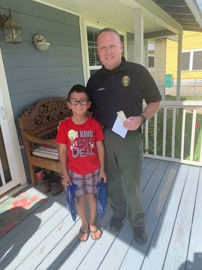 David Jimenez and Conroe Police Chief Jeff Christy pose for a Aug. 27 picture outside the 7-year-old's home in Conroe. The second grader wrote a letter sending police thanks for their work. Photo: Courtesy Of The Conroe Police Department