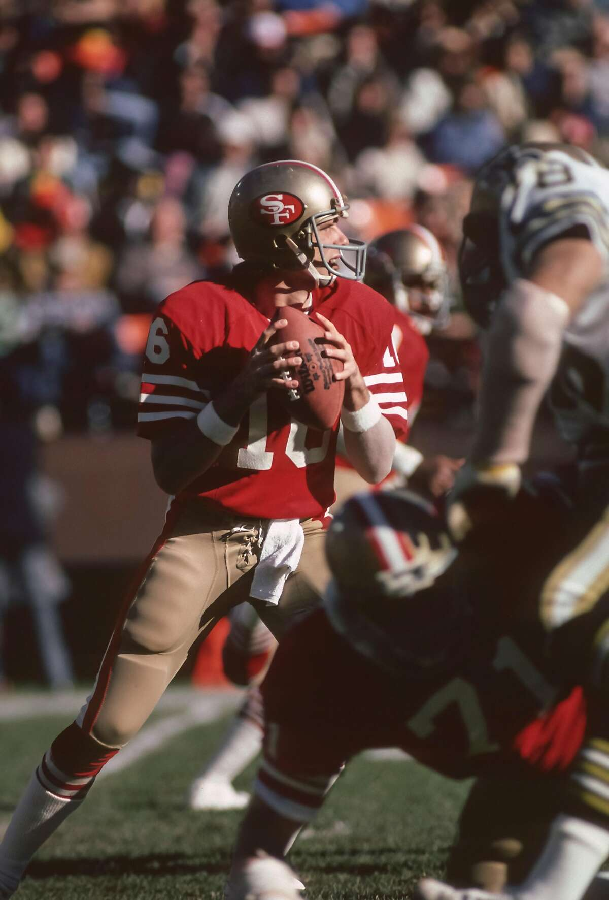 Joe Montana #16 of the San Francisco 49ers attempts a pass during an NFL game against the New Orleans Saints played on December 7, 1980 at Candlestick Park in San Francisco, California.