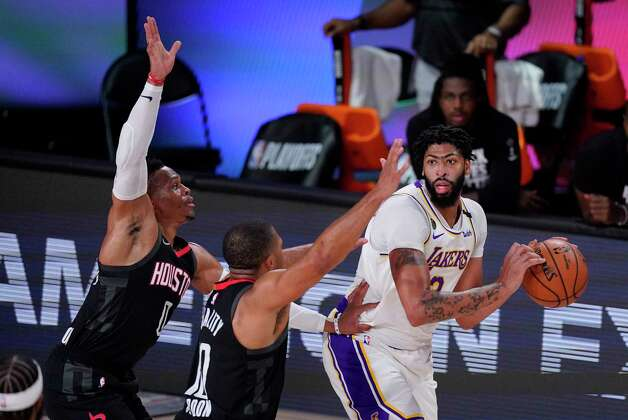 Los Angeles Lakers' Anthony Davis, right, passes around Houston Rockets' Russell Westbrook, left, and Eric Gordon during the second half of an NBA conference semifinal playoff basketball game Tuesday, Sept. 8, 2020, in Lake Buena Vista, Fla. (AP Photo/Mark J. Terrill) Photo: Mark J. Terrill, Associated Press / Copyright 2020 The Associated Press. All rights reserved.