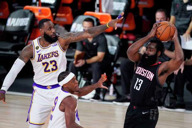 Houston Rockets' James Harden (13) passes over Los Angeles Lakers' LeBron James (23) and Rajon Rondo during the first half of an NBA conference semifinal playoff basketball game Tuesday, Sept. 8, 2020, in Lake Buena Vista, Fla. (AP Photo/Mark J. Terrill) Photo: Mark J. Terrill, Associated Press / Copyright 2020 The Associated Press. All rights reserved.