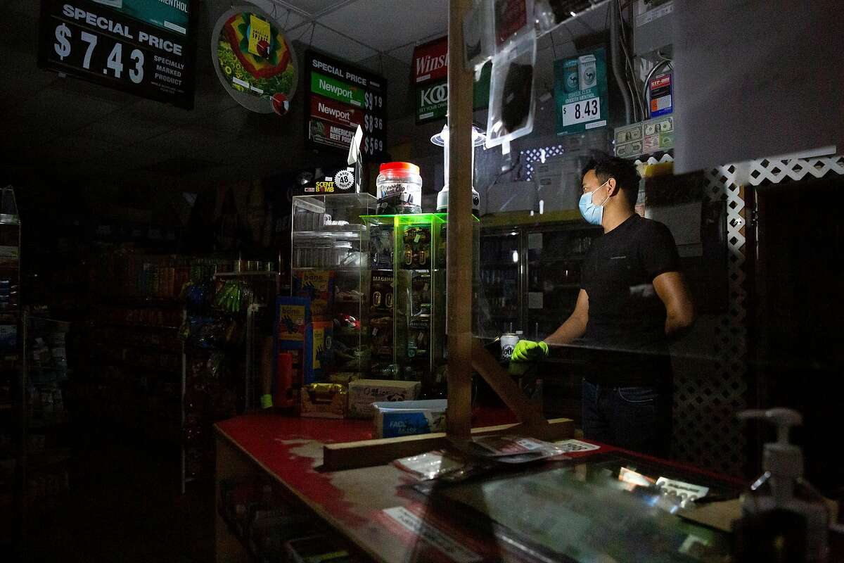 Manendra Champ is lit by a camping light as he stands behind the counter at the Fast and East Market and Gas Station in Calistoga on Tuesday, September 8, 2020. The gas station was just one of many businesses without power for the day as PG&E continues to shut off power to portions of the North Bay following red flag warnings due to high heat and wind conditions throughout the Bay Area.