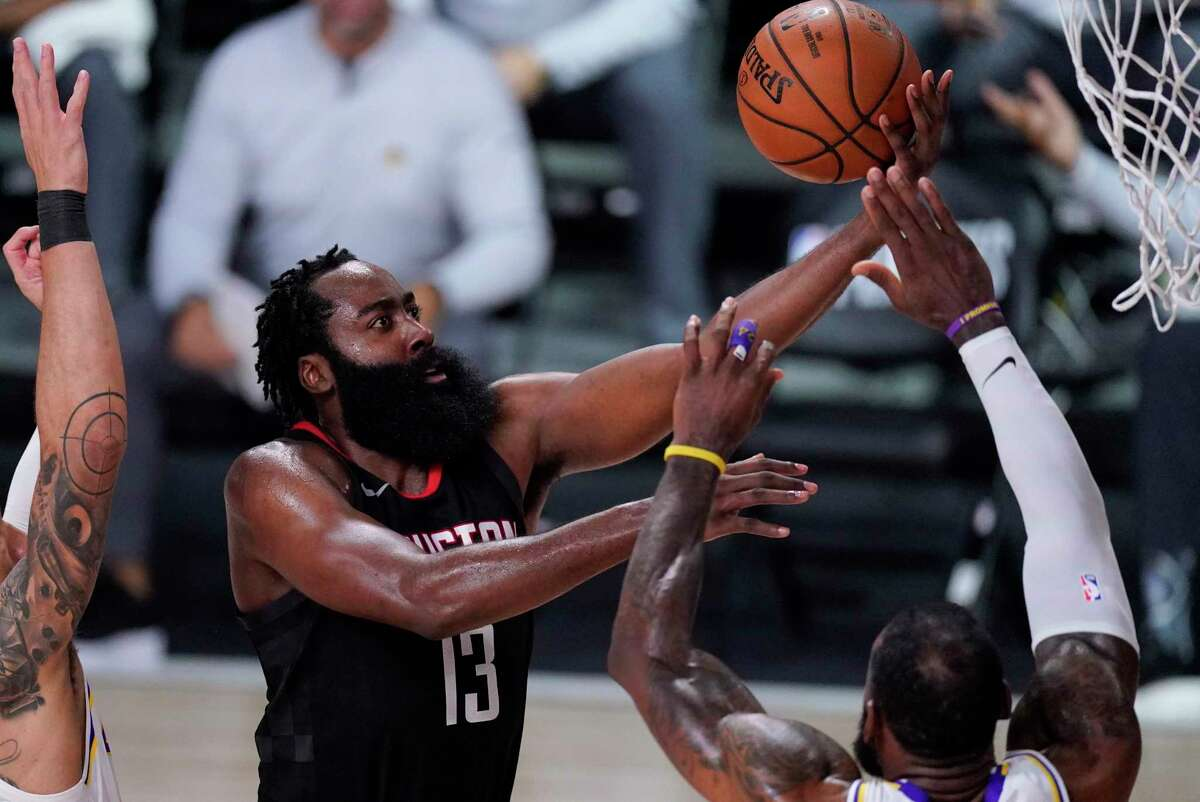 Houston Rockets' James Harden (13) drives to the basket over Los Angeles Lakers' LeBron James, right, during the second half of an NBA conference semifinal playoff basketball game Tuesday, Sept. 8, 2020, in Lake Buena Vista, Fla. (AP Photo/Mark J. Terrill)