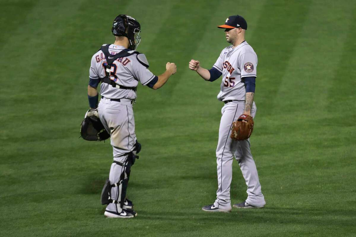Houston Astros' Ryan Pressly, right, celebrates with Dustin Garneau after the Astros defeated the Oakland Athletics during the second baseball game of a doubleheader in Oakland, Calif., Tuesday, Sept. 8, 2020. (AP Photo/Jed Jacobsohn)