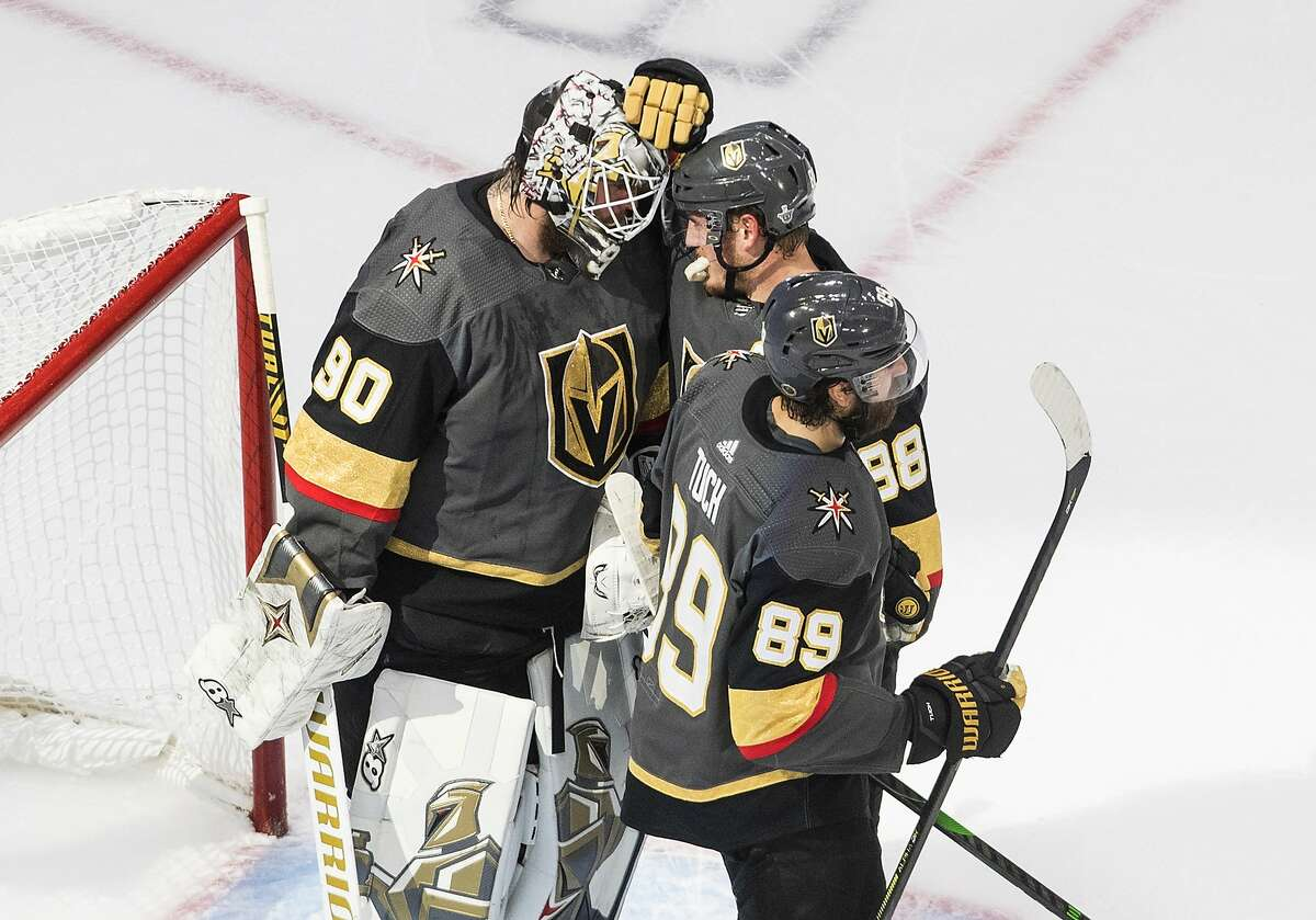 Vegas Golden Knights goalie Robin Lehner (90) and teammates Nate Schmidt (88) and Alex Tuch (89) celebrate the team's 3-0 win over the Dallas Stars in Game 2 of the NHL hockey Western Conference final, Tuesday, Sept. 8, 2020, in Edmonton, Alberta. (Jason Franson/The Canadian Press via AP)