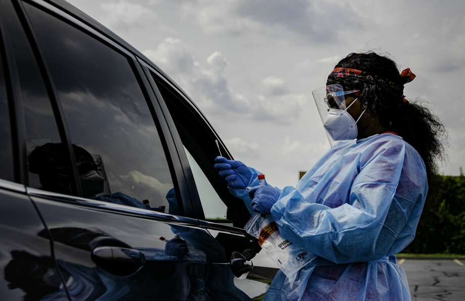 Phlebotomist Kainna Berry finishes testing a patient for COVID-19 at the drive-thru testing site hosted by the Madison County Health Department on Tuesday at the Gateway Convention Center in Collinsville. Photo: Tyler Pletsch   The Intelligencer