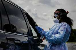 Phlebotomist Kainna Berry finishes testing a patient for COVID-19 at the drive-thru testing site hosted by the Madison County Health Department on Tuesday at the Gateway Convention Center in Collinsville.