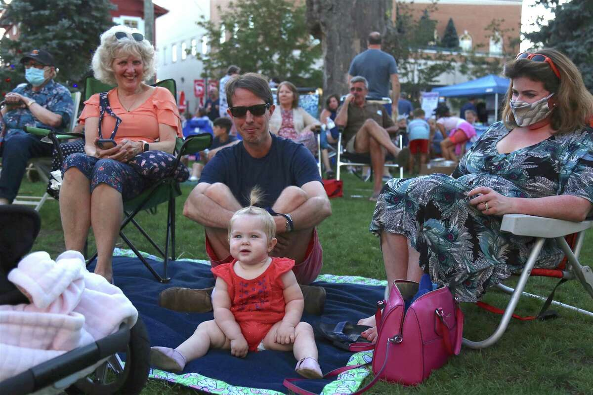 Grandmother Mary Ann Hau, left, Bill and Emily Hau, and Bizzy, 10 months, all of Fairfield, enjoy the show at the KJD fundraiser concert on Sherman Green on Saturday, Sept. 5, 2020, in Fairfield, Conn.