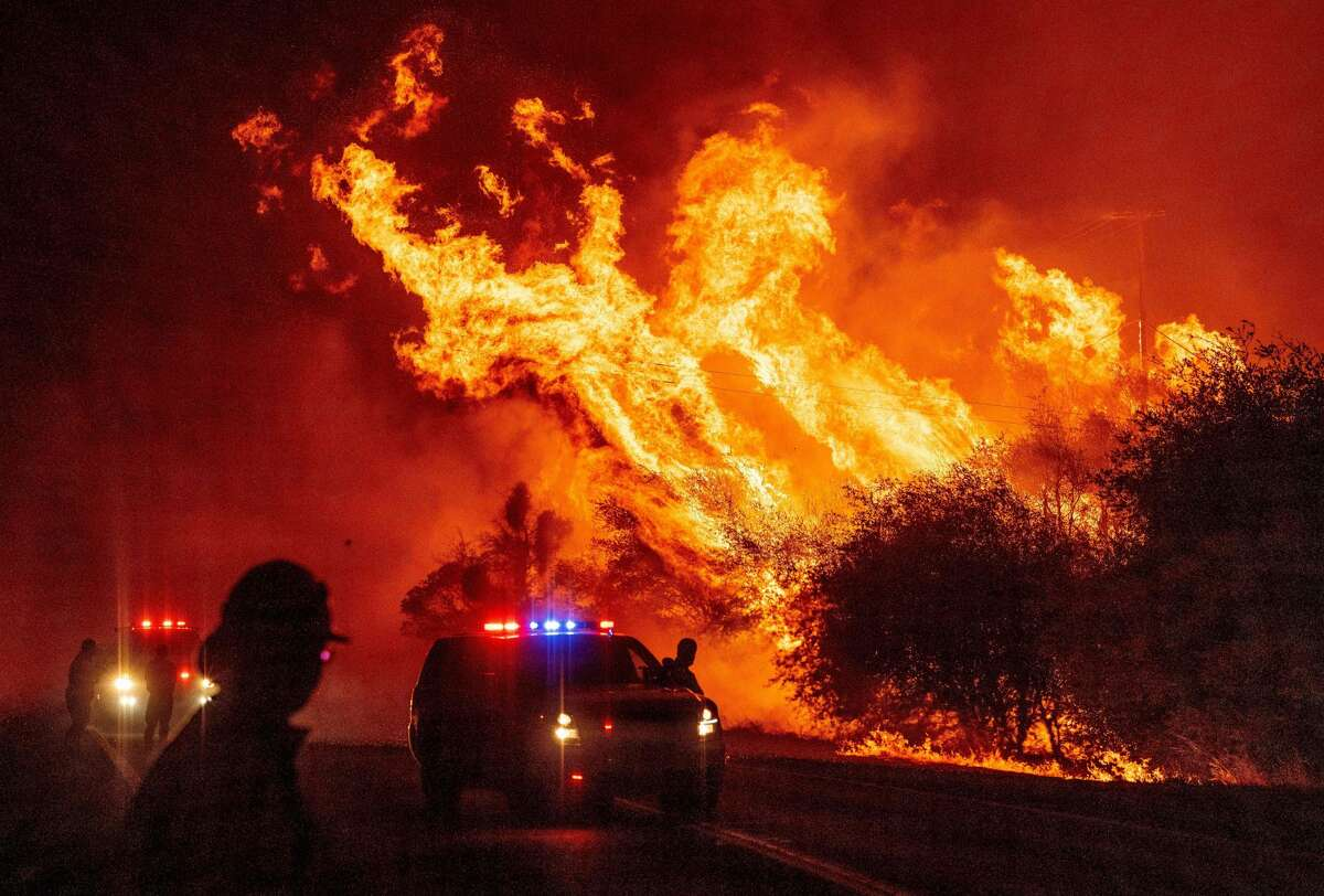 A law enforcement officer watches flames launch into the air as fire continues to spread at the Bear fire in Oroville, California on September 9, 2020