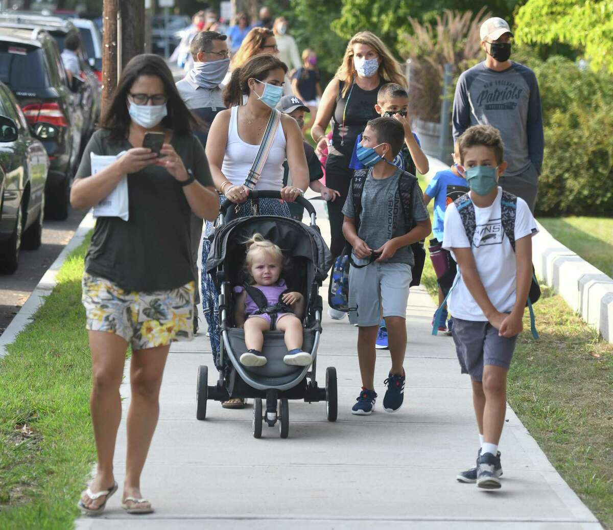 Parents walks their kids to school on the first day of the 2020-2021 school year at Old Greenwich School in Old Greenwich, Conn. Wednesday, Sept. 9, 2020. As a result, students and parents expressed a new ambivalence to the first day of school.