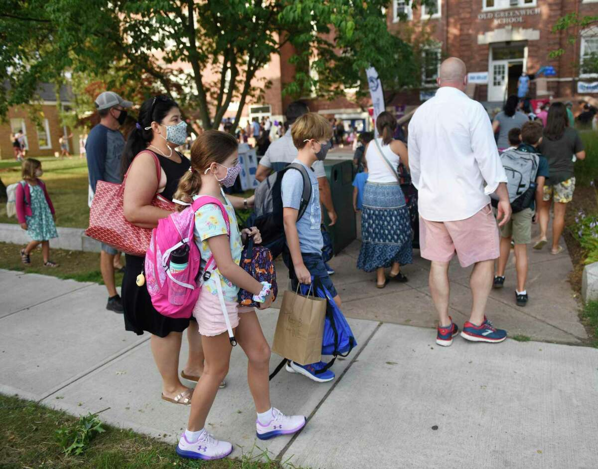 Parents walks their kids to school on the first day of the 2020-2021 school year at Old Greenwich School in Old Greenwich, Conn. Wednesday, Sept. 9, 2020. Al Keshvarzian, who was dropping off his daughter at Old Greenwich and also has a son in middle school, credited the district for its communication of changes and safety protocols.