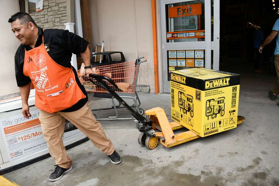 A worker helps residents at Home Depot where they are buying generators during hurricane season. Photo: MICHELE EVE SANDBERG/AFP Via Getty Images