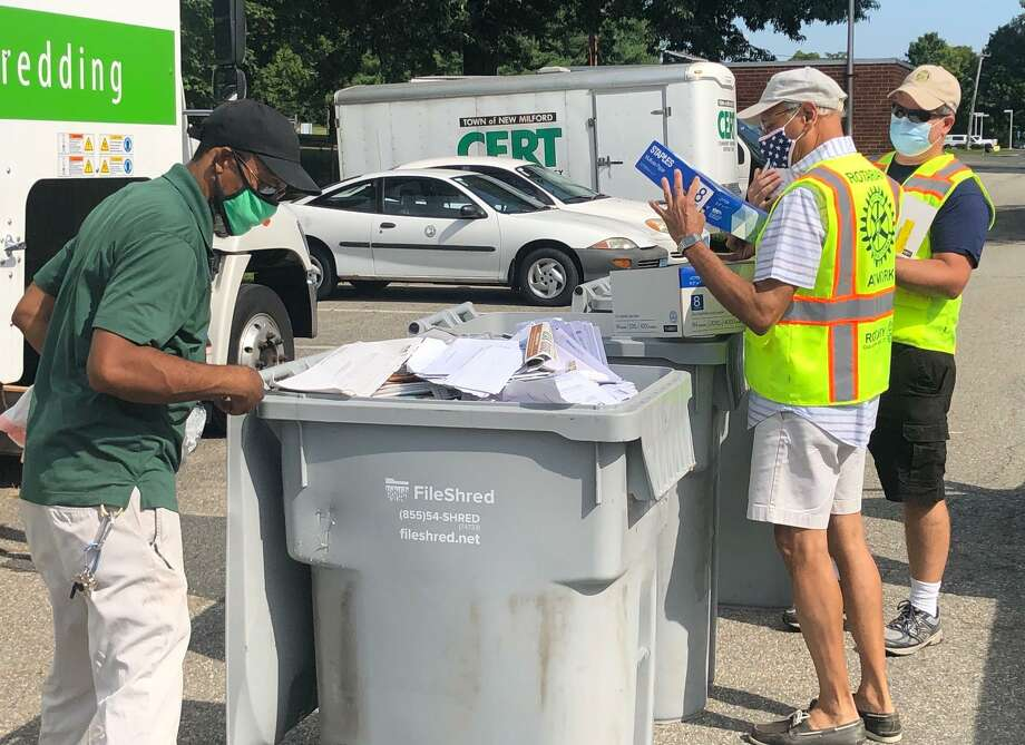A FileShred employee, left, prepares a bin of paper to be shredded as Rotarians Mansoor Haidary and Ralph Williams, right, prepare to unload of box of papers into the bin. Photo: Deborah Rose /Hearst Connecticut Media / Danbury News Times